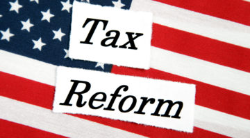 The words Tax reform sitting on an American flag tax relief