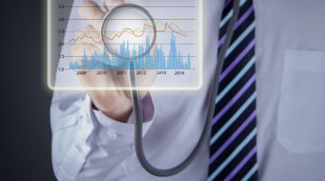 Businessman using stethoscope to diagnose business charts profit revenue review