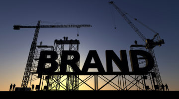 Backlit silhouette of a construction site with cranes and steel structures building the word brand branding